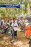 Teen boy stops to think as children leave primary Cambodian school with banner in French and Cambodian through gate on bicycles and motorcycles in Siem Reap, Cambodia