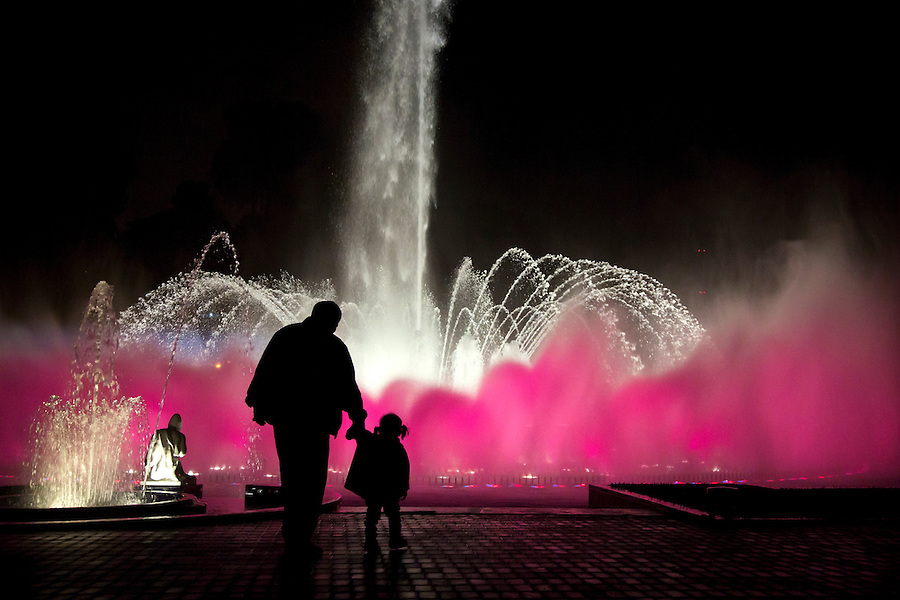 A man and his daughter are silhouetted by a lit-up fountain at Reserva Park in Lima, Peru.