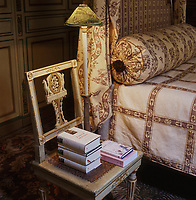 One of a set of four Louis XVI painted chairs is positioned at a corner of the master bed and acts as a bedside table