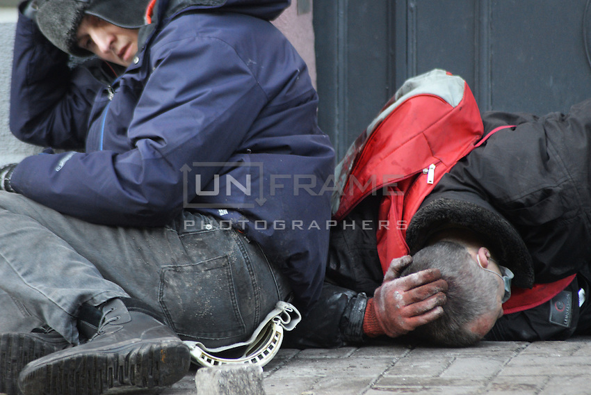 Prostesters take cover from bullets rounds on the battlefield of Maidan square.  Kiev, Ukraine
