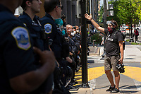 A demonstrator speaks to police officers near the White House in Washington D.C., U.S., as crews clean Black Lives Matter Plaza on Tuesday, June 23, 2020.  Trump tweeted that he authorized the Federal government to arrest any demonstrator caught vandalizing U.S. monuments, with a punishment of up to 10 years in prison.  Credit: Stefani Reynolds / CNP/AdMedia