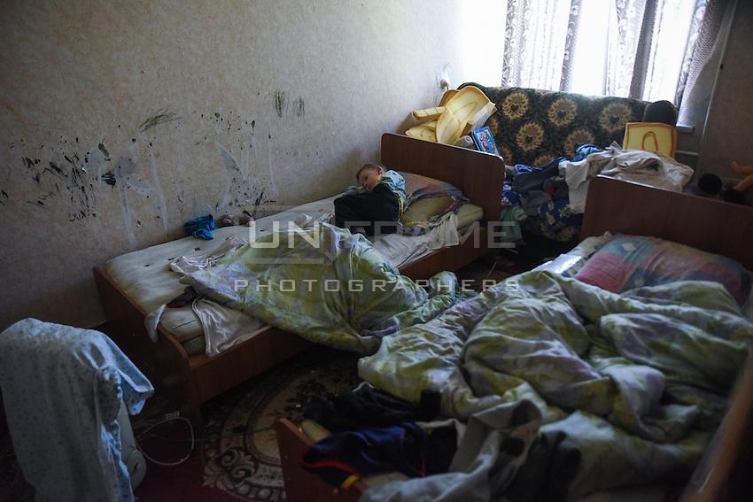 Little Anton sleeps on the bed of the dormitory for IDPs in Stakhanov, Eastern Ukraine, Thursday, May 21, 2015
