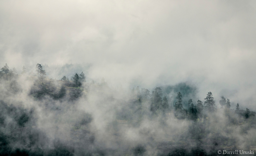 Photograph of fast moving clouds as they travel across the mountain tops in the South Okanagan Valley in British Columbia, Canada.