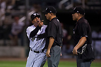 Idaho Falls Chukars manager Omar Ramirez (11) voices his discontent with home plate umpire Ethan McCranie as field umpire Edgar Suarez tries to keep separation during a Pioneer League game against the Great Falls Voyagers at Melaleuca Field on August 18, 2018 in Idaho Falls, Idaho. The Idaho Falls Chukars defeated the Great Falls Voyagers by a score of 6-5. (Zachary Lucy/Four Seam Images)