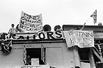 Pro supporters of the Falkland war hang banners from a Whitehall building London, as an anti falklands war demo passes underneath. London May 1983. 'CND <br /> Communists Neutralists, Defeatists',  'Britain Rules OK' 'Patriotism NOT Treason'