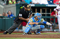 UCLA catcher Shane Zeile (14) and umpire Billy Speck (22) against the North Carolina State Wolfpack during Game 8 of the 2013 Men's College World Series on June 18, 2013 at TD Ameritrade Park in Omaha, Nebraska. The Bruins defeated the Wolfpack 2-1, eliminating North Carolina State from the tournament. (Andrew Woolley/Four Seam Images)