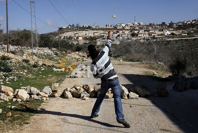 Palestinian youths hurl stones at Israeli security forces ,during a protest in the village of Kufr Qaddum near the Israeli settlement of Kdumim, in the northern West Bank, Friday, Dec. 23, 2011 . Photo by Wagdi Eshtayah.