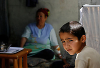 """Gaza.June.22.2008 Um suhil 72 years prepar food for her children, Um Suhail says: """"we got used to live among the graves of the deadÖ we are like them; depending on charities and handouts.""""""""The family was drove out from their original village in the 1948 when Jews forced thousands of Palestinians to migrate, establishing the State of Israe.June.22.2008l.""""photo by Fady Adwan/propaimages"""""""