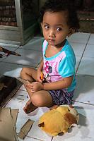 Bali, Indonesia.  Little Balinese Girl and her Stuffed Animal.  Tenganan Village.