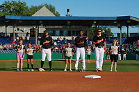 Batavia Muckdogs Andrew Turner, Dalvy Rosario, and Nic Ready stand for the national anthem with young fans before a NY-Penn League game against the State College Spikes on July 1, 2019 at Dwyer Stadium in Batavia, New York.  Batavia defeated State College 5-4.  (Mike Janes/Four Seam Images)