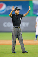Umpire Takahito Matsuda calls for time during the Appalachian League game between the Pulaski Mariners and the Burlington Royals at Burlington Athletic Park on July 20, 2013 in Burlington, North Carolina.  The Royals defeated the Mariners 6-5.  (Brian Westerholt/Four Seam Images)