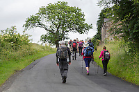 Cumbria, England, UK.  Hikers on Hadrian's Wall Footpath approaching Village of Banks.