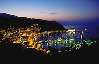 Overview of Avalon Harbor at dusk with boats in the marina and the Pacific Ocean stretching into the distance. Catalina Island, California.