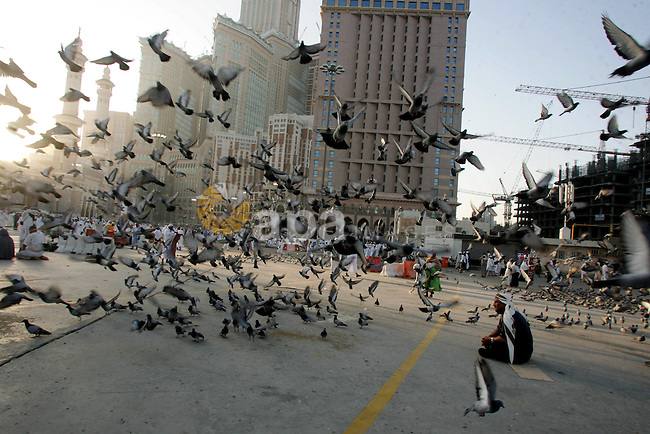 Muslim pilgrim feed the doves outside the Grand Mosque during the annual Hajj in Mecca, Saudi Arabia, Nov 9, 2010. Some 2.5 million Muslims from more than 160 countries converge annually on the Islamic cities of Mecca and Medina in western Saudi Arabia for the hajj pilgrimage. Photo by Mahfouz Abu Turk