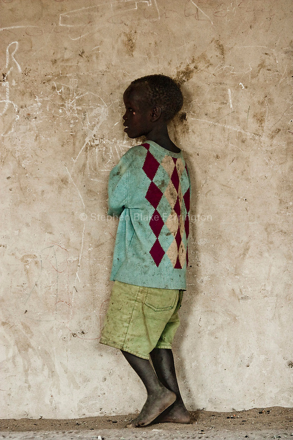 Africa, Sudan, Magwi County, Nimule, Southern Sudan - A young boy on the veranda at an orphanage in Nimule. December 2005 © Stephen Blake Farrington