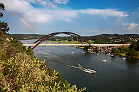 A beautiful rainbow towers over the 360 Bridge as ski boaters take to the waters of Lake Austin. Water skiing is a favorite year round pastime on Lake Austin.