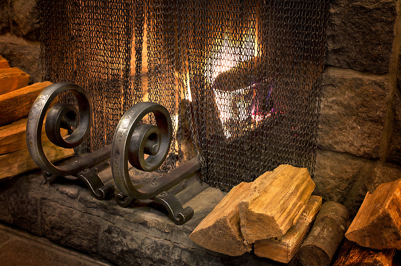 Fire in fireplace with wrought iron grate. Timberline Lodge, Oregon