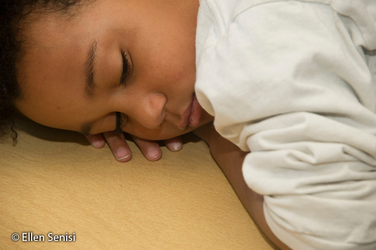 MR / Schenectady, New York. Yates Arts-in-Education Magnet School (urban public school). First grade classroom. Student (boy, 6, bi-racial) rests at his desk. MR: Gig1. ID: AM-g1w. © Ellen B. Senisi.