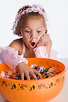 USA, Illinois, Metamora, Girl (6-7) in costume taking candies from bowl and making face
