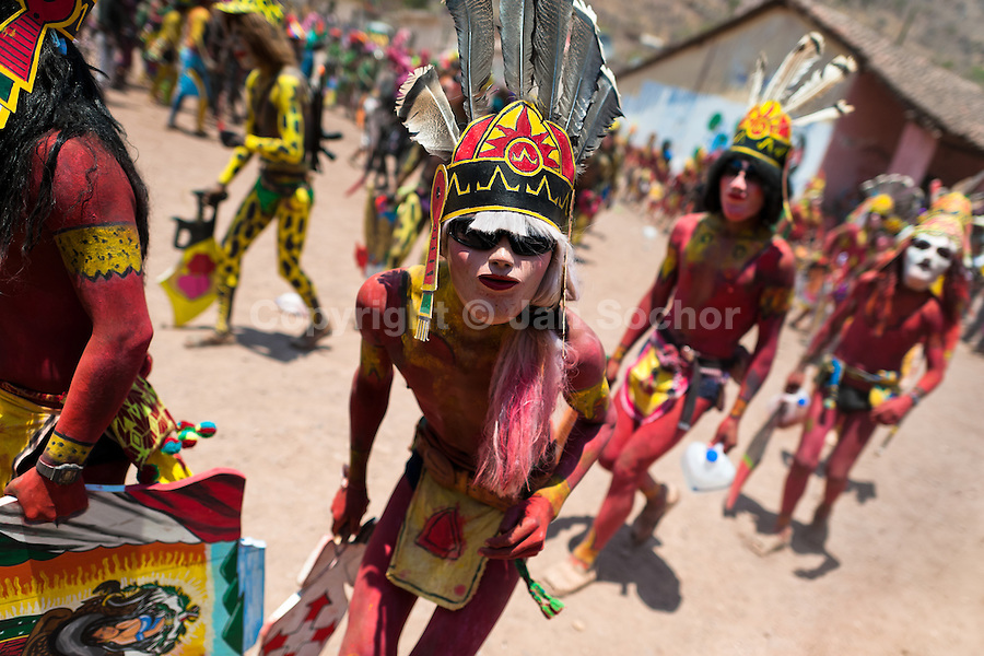 """Cora Indians, wearing colorful masks, run during the religious ritual celebration of Semana Santa (Holy Week) in Jesús María, Nayarit, Mexico, 22 April 2011. The annual week-long Easter festivity (called """"La Judea""""), performed in the rugged mountain country of Sierra del Nayar, merges indigenous tradition (agricultural cycle and the regeneration of life worshipping) and animistic beliefs with the Christian dogma. Each year in the spring, the Cora villages are taken over by hundreds of wildly running men. Painted all over their semi-naked bodies, fighting ritual battles with wooden swords and dancing crazily, they perform demons (the evil) that metaphorically chase Jesus Christ, kill him, but finally fail due to his resurrection. La Judea, the Holy Week sacred spectacle, represents the most truthful expression of the Coras' culture, religiosity and identity."""
