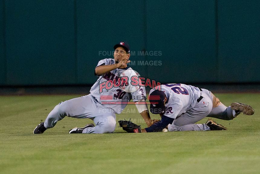 Angel Castillo (30) and Roberto Lopez (20) of the Arkansas Travelers collide while diving for a fly ball to right center field during a game against the Springfield Cardinals at Hammons Field on June 13, 2012 in Springfield, Missouri. (David Welker/Four Seam Images)