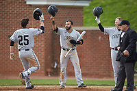Spencer Packard (25) of the Campbell Camels is greeted at home plate by teammates Luis Gimenez (14) and Collin Wolf (4) after hitting a 2-run home run against the High Point Panthers at Williard Stadium on March 16, 2019 in  Winston-Salem, North Carolina. The Camels defeated the Panthers 13-8. (Brian Westerholt/Four Seam Images)
