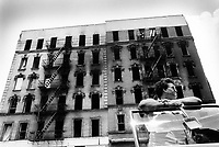 USA. New York City. Spanish Harlem. Puerto Rican family. Pat holds a  child's toy in her hand while standing near her car's door. Wreck of a derelict and burned out building. The family lives below the poverty line and receives public assistance (AFDC, Home Relief, Supplemental Security Income and Medicaid). Spanish Harlem, also known as El Barrio and East Harlem, is a low income neighborhood in Harlem area. Spanish Harlem is one of the largest predominantly Latino communities in New York City. 28.06.88 © 1988 Didier Ruef .