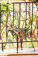 A black wire metal chair on a terrace balcony with garden vegetation in the background Clos des Iles Le Brusc Six Fours Cote d'Azur Var France