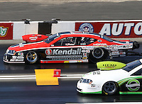 Feb. 17, 2013; Pomona, CA, USA; NHRA pro stock driver V. Gaines (left) races alongside Deric Kramer during the Winternationals at Auto Club Raceway at Pomona. Mandatory Credit: Mark J. Rebilas-
