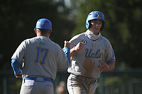 JT Schwartz (7) of the UCLA Bruins is greeted by third base coach Rex Peters after hitting a home run during a game against the USC Trojans at Dedeaux Field on March 28, 2021 in Los Angeles, California. UCLA defeated USC, 13-1. (Larry Goren/Four Seam Images)