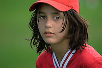 Adolescent girl with dark brown hair in red baseball cap and red shirt on green grass.<br />