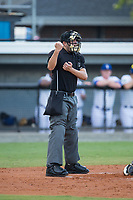 Home plate umpire Ben Fernandez makes a strike call during the Appalachian League game between the Danville Braves and the Burlington Royals at Burlington Athletic Stadium on August 15, 2017 in Burlington, North Carolina.  The Royals defeated the Braves 6-2.  (Brian Westerholt/Four Seam Images)