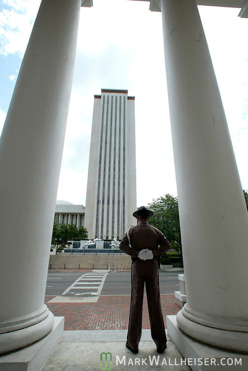 A guard stand watch on the porch of the Florida Supreme Court building with the new Florida State capitol building in the background in downtown Tallahassee, Florida May 17, 2004.    (Mark Wallheiser/TallahasseeStock.com)