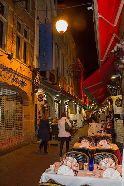 Women walking along an outdoor restaurant near the Great Square, Brussels, Belgium,