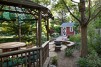 Stone patio between gazebo under shade tree and tool shed in Habets garden, California