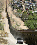 A U.S. Border Patrol agent patrols along the fence line of the U.S.-Mexico border in Nogales, Ariz., on Thursday, April 6, 2006.  (photo by Khampha Bouaphanh)