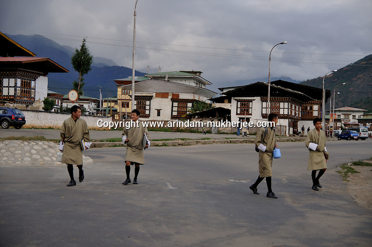 Young Bhutanese boys wearing Gho (the national dress) coming back from school at the city of Paro. West Bhutan. Arindam Mukherjee