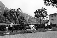 Switzerland. Ticino. Lugano. A father seats on a bench while the mother takes care of their child playing in a public playground located in Pregassona, a quarter of the city of Lugano. Couple life. 8.05.99 © 1999 Didier Ruef