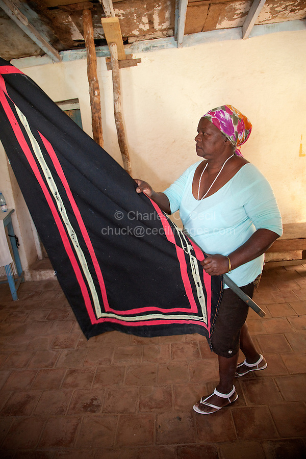 Cuba, Trinidad.  Woman Carrying Red, Yellow, and Black Flag in Afro-Cuban Religious Ceremony of Congolese Origin.