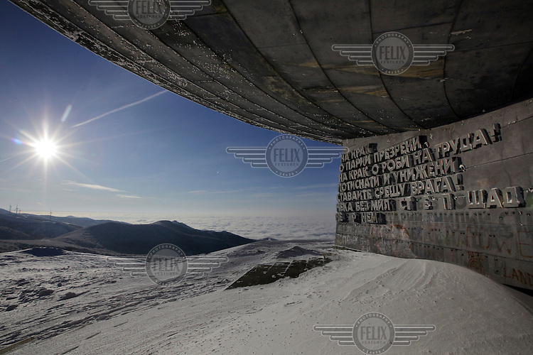 Verses of The International and The Worker's March inscribed on the entrance of the Buzludzha Monument, communist era Bulgarias architectural pean to its socialist roots. The monument was built at the top of Mount Buzludzha, in the Balkan Mountain range, at the spot where a band of Bulgarian nationalists were defeated by Ottoman forces in 1868 and, in 1891, a secret assembly founded Bulgarias socialist movement. After a seven year period of construction it was finally unveiled in 1981. 6000 workers toiled to realise architect Gueorguy Stoilovs design that incuded a main hall containing 500 sq metres of mosaic fresco depicting, among others, Marx, Engels, Lenin and the Bulgarian communist leader Todor Zhivkov. In 1989, following the collapse of communist rule in Bulgaria, the monument was left to ruin and since then many of its valuable construction materials have been looted. Today, the derelict building stands as an iconic monument to an abandoned ideology.
