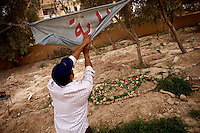 Syria, Deir az-Zor, 2013/03/17..A man unfolds a banner hanging between trees on a former playground which now serves as a cemetery for victims of shelling and fighting in Deir az-Zor. .Syrie, Deir ez-Zor, 17/03/2013.Un homme déroule une banderole suspendue entre les arbres sur un anicen terrain de jeu qui sert maintenant de un cimetière pour les victimes des bombardements et des combats à Deir ez-Zor..Photo : Timo Vogt / Est&Ost Photography.