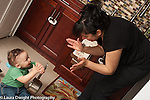 10 month old baby boy sitting on kitchen floor clapping hands as mother leans over to clap with him