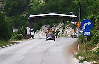 The border crossing between Montenegro and Bosnia-Herzegovina. A car approaching the border control checkpoint where a guard is waiting. Trebinje region. Republika Srpska. Bosnia Herzegovina, Europe.