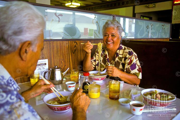 Senior Hawaiian man and part-Hawaiian woman in restaurant eating wo gau gee mein (dumplings, pork, shrimp, vegetables, noodles) with chopsticks; Kaneohe, Windward Oahu