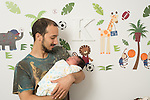 1 week old newborn baby boy asleep at home held by father