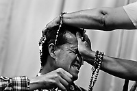 A Colombian pastor, pressing a crucifix on a believer's head, attempts to evict a supposed demon during the exorcism ritual performed at a house church in Bogota, Colombia, 10 March 2016. Hundreds of Christian belivers, joined in nameless groups, gather every week in unmarked home churches dispersed in the city outskirts, to carry out prayers of liberation and exorcism. Community members and their religious activities are usually conducted by a charismatic pastor or preacher. Using either non-contactive methods (reading religous formulas from bible, displaying Christian symbols and icons) or rough body-pressure-points techniques and forced burping, a leading pastor commands the supposed evil spirit, which is generally believed to come from witchcraft, to depart a person's mind and body. The demon's expulsion often consists of multiple rites and may last for several months.
