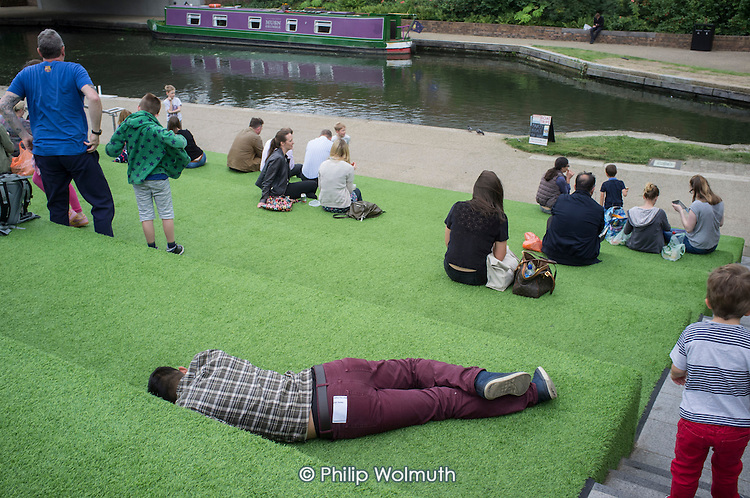 Young man sleeping on artificial grass landscaping by the Grand Union canal, King's Cross, London. About 40% of the newly re-developed 67-acre site is deemed public space, although the entire site is privately owned and managed.
