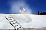 ROTTERDAM - Een bouwvakker met stofmasker, stofbril en geluidskappen op, schuurt met een schuurmachine beton.  COPYRIGHT TON BORSBOOM