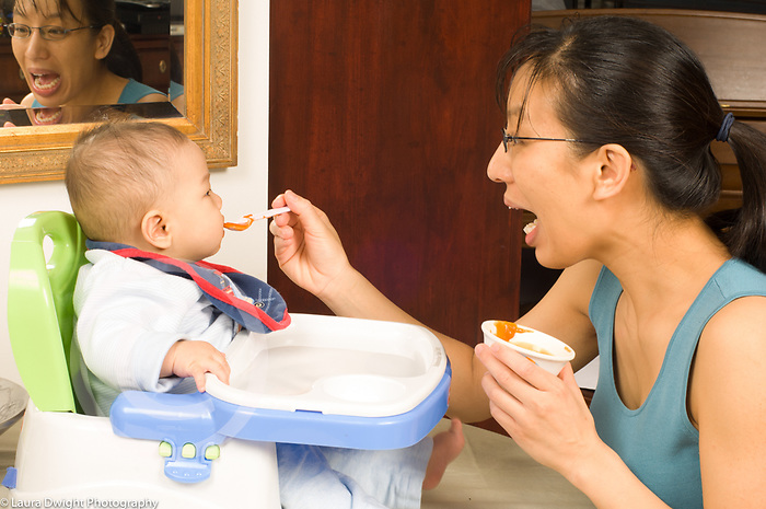6 month old baby boy in infant seat fed solid food by mother Asian American Chinese