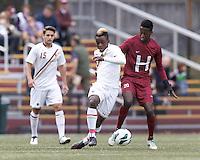 Boston College midfielder Derrick Boateng (10) dribbles as Harvard University forward Ashi Geberkidane (20) defends.Boston College (white) defeated Harvard University (crimson), 3-2, at Newton Campus Field, on October 22, 2013.